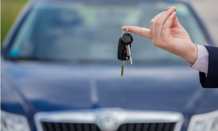 A car dealer holding car keys in front of a used car for sale